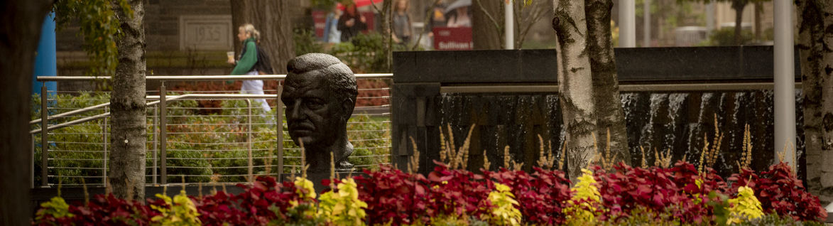 A bust of Temple's founder and first president, Russel Conwell, is surrounded by flowers and a water fountain.