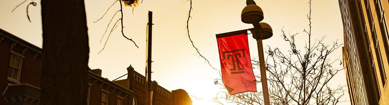 The sun setting behind a flag on Temple's Main Campus.